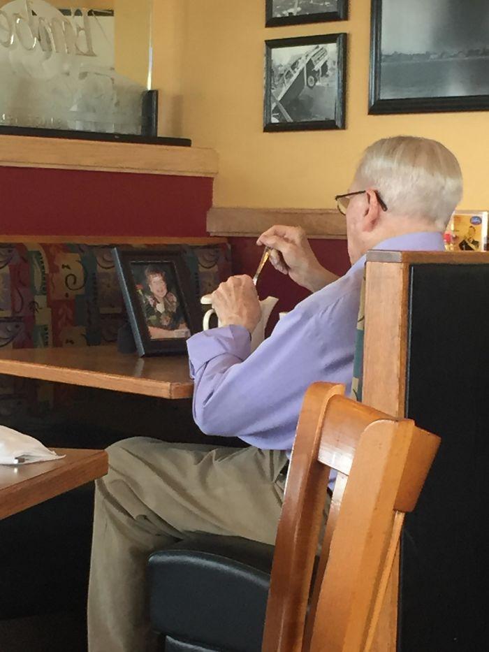 señor con foto de esposa en restaurante