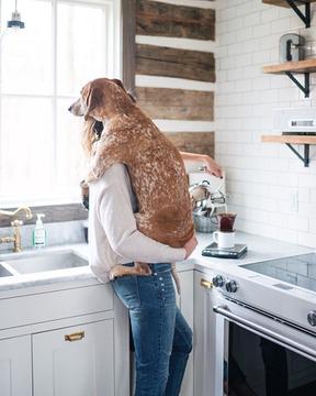 chica con perrito en la cocina