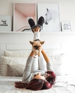 chica jugando con perrito en la cama