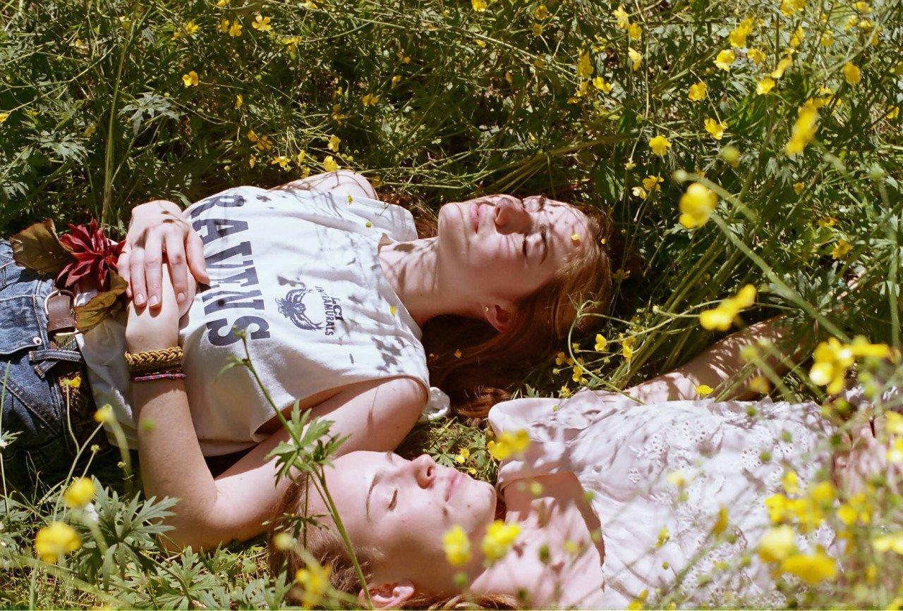 chicas tiradas en el pasto disfrutando de la naturaleza