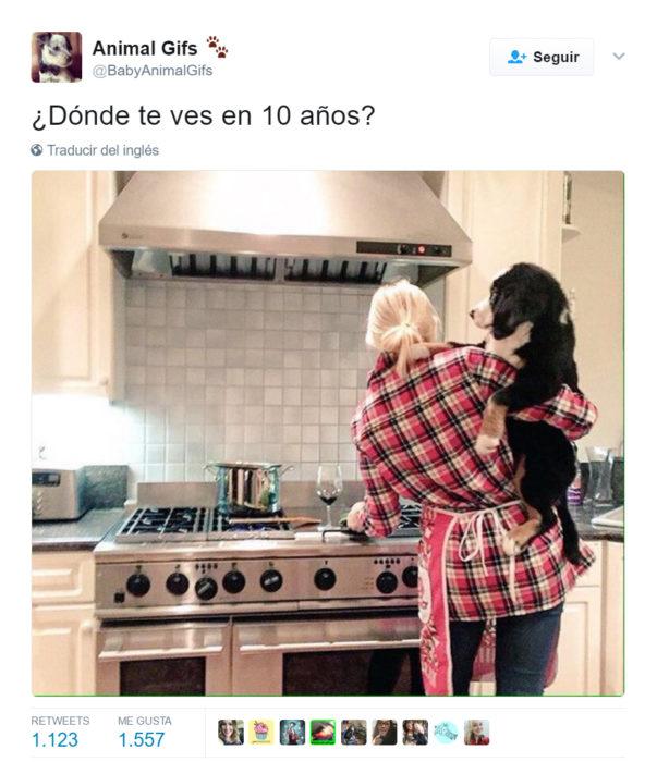 Chica cargando a un perro mientras cocina