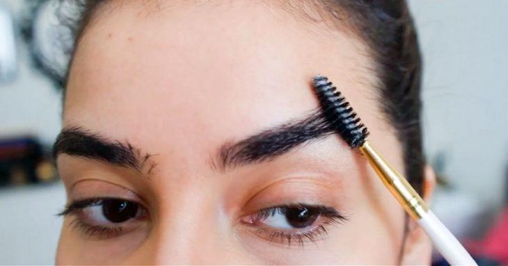 mujer cepillando sus cejas