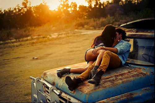 pareja besándose sobre una camioneta