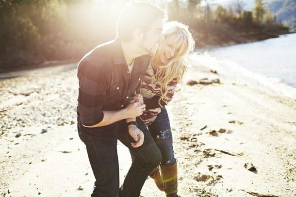 pareja riéndose en la playa a contra luz