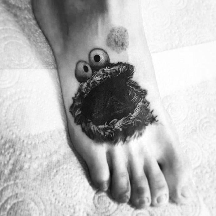 Chico con un tatuaje del monstruo come galletas en el pie