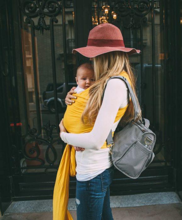 mujer rubia cargando a un bebé