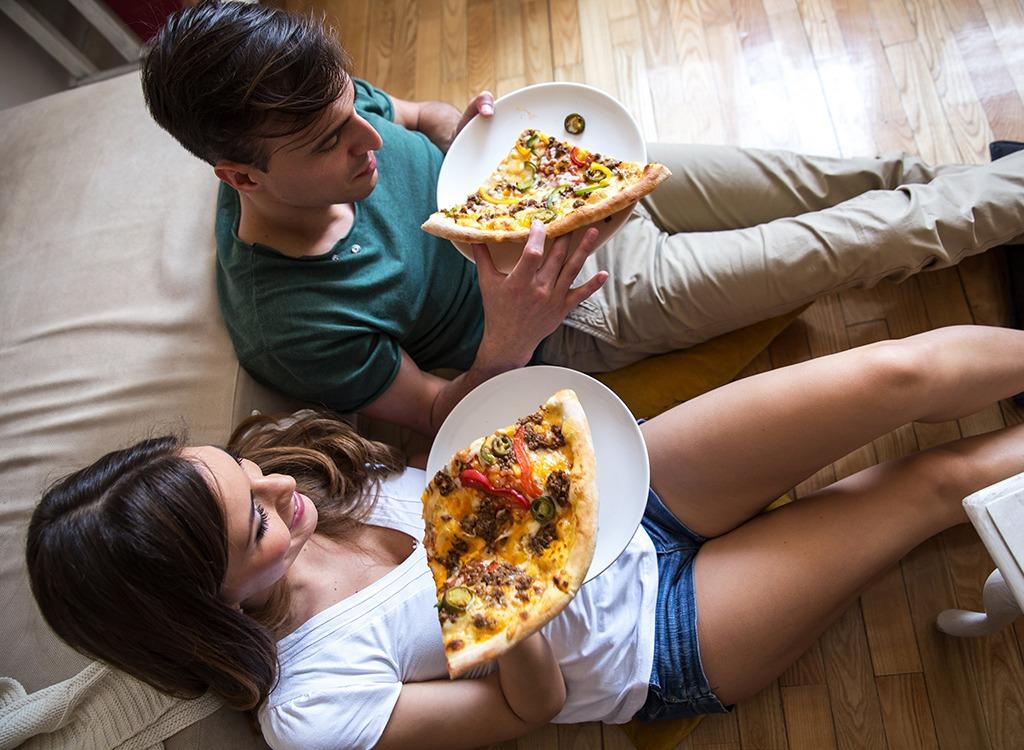 pareja sentados en el piso comiendo pizza