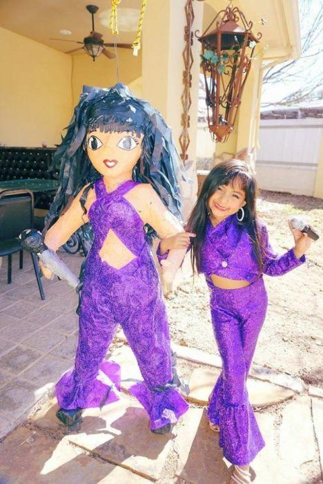 niña con ropa morada al lado de piñata