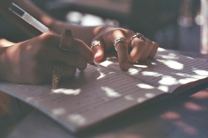 mujer escribiendo con anillos