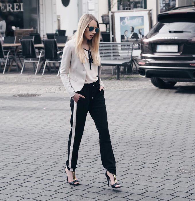 Chica usando unos track pants en color negro con un saco beige