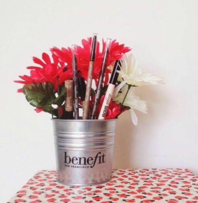 frasco con flores y maquillaje