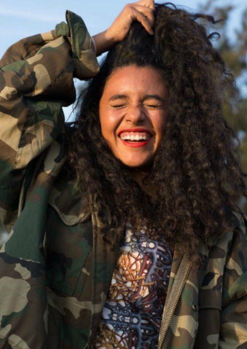 mujer sonriendo con cabello chino