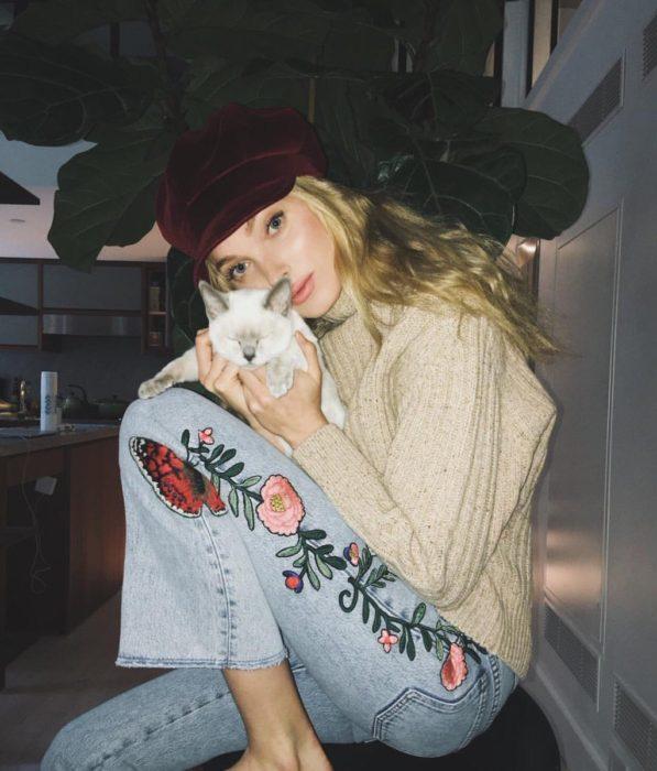 chica con gato y pantalon bordado de flores