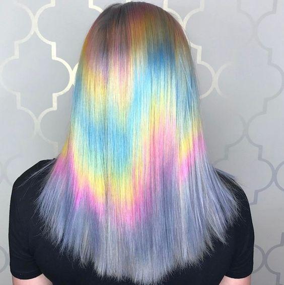 Chica de espaldas mostrando su cabello con efecto holografico en tonos pastel
