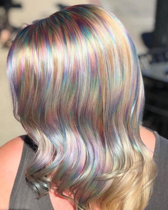 Chica con cabello rubio platinado y mechas de efecto holografico en tonos pastel