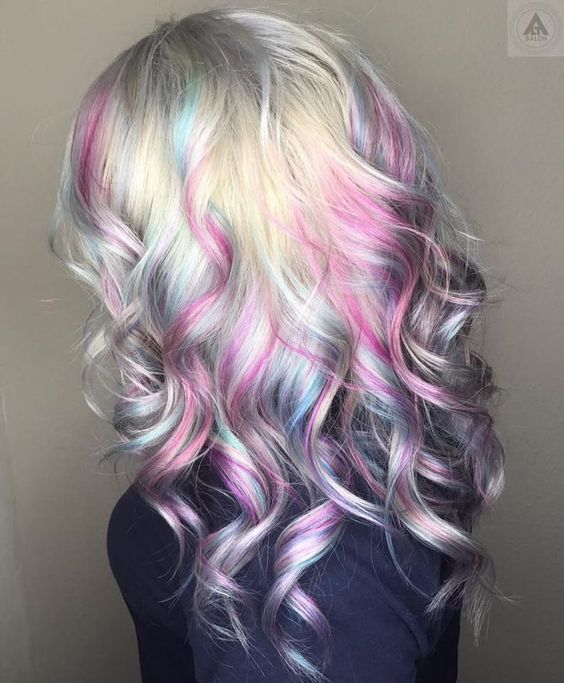 Chica de perfil mostrando su cabello con efecto holografico en tonos rosa pastel