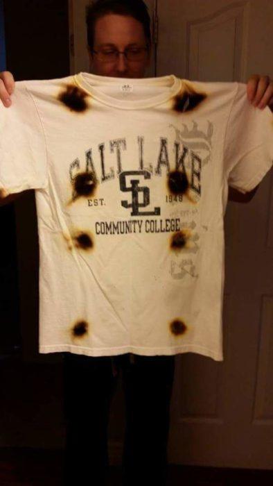 Hombre sosteniendo una camisa quemada