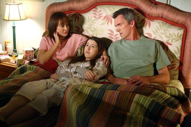 escena de la serie the middle padres recostados junto a su hija