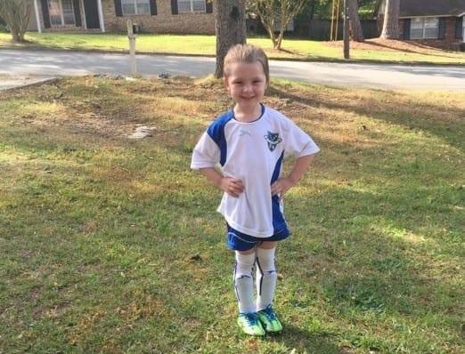 Niña de 4 años que juega fútbol