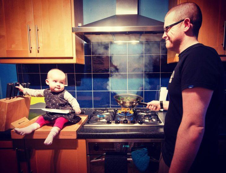 Niña en la cocina cocinando junto a su padre