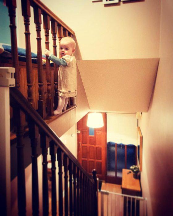 Niña sujetada del barandal de las escaleras