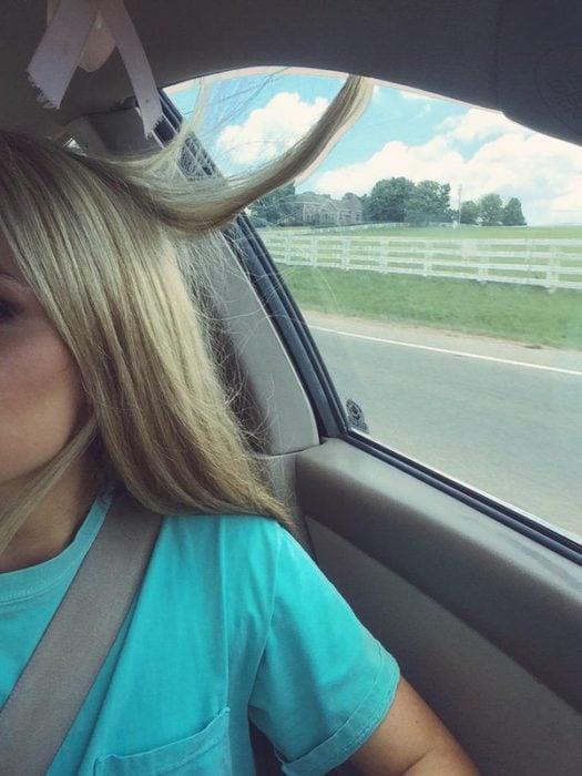 Chica con el cabello atorado en el vidrio del carro