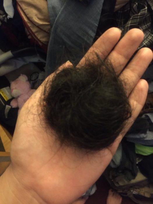 Chica sosteniendo una bola de cabello en su mano