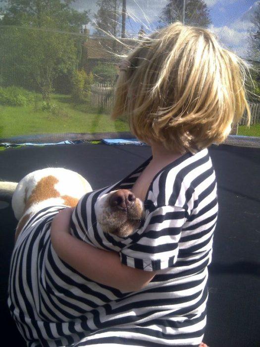 niño cubriendo a su perro