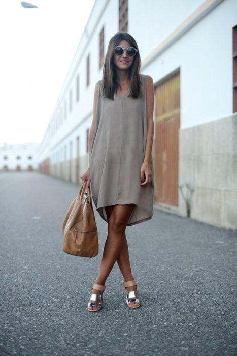 Chica usando un vestido y sandalias metalicas