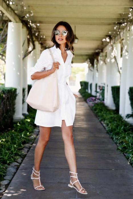 Chica usando unas sandalias de color blanco con un vestido del mismo color
