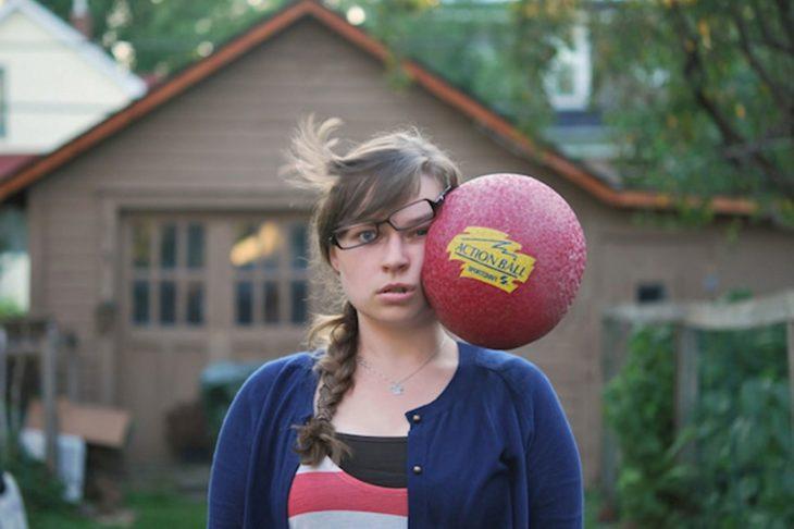 Chica con un balón en su cara
