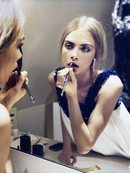 Chica maquillandose frente a un espejo