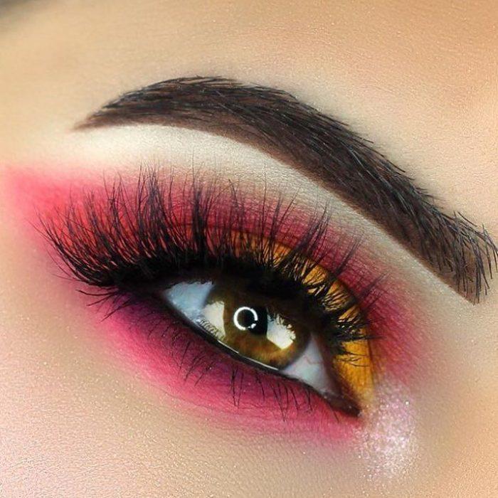 Ojo de una chica maquillada en tonos rosas