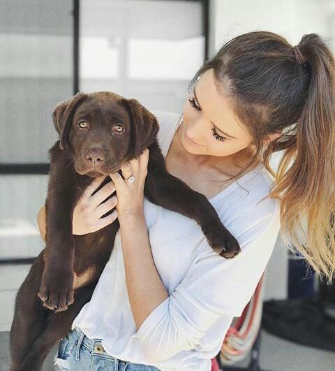 chica cargando a su perrito café