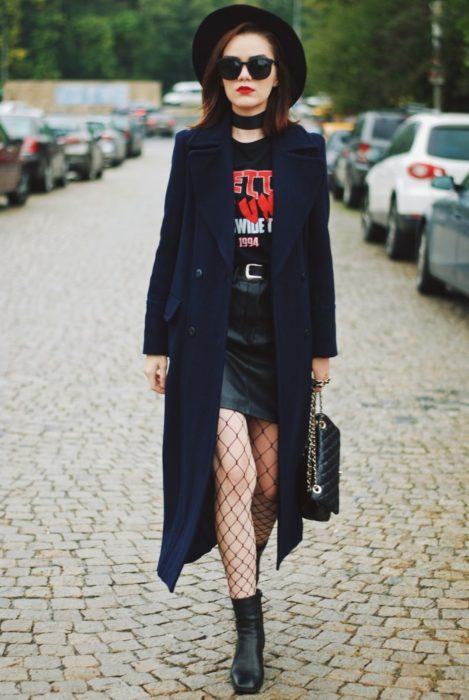 Chica usando medias de red con una falda de cuero