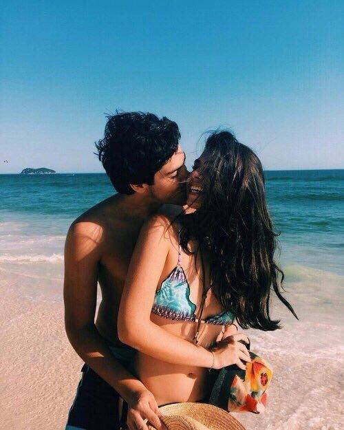 pareja besandose en la playa