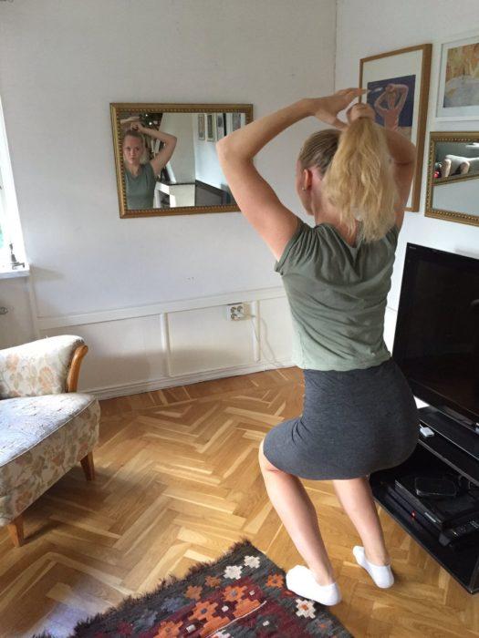 Chica alta intentando peinarse en un espejo bajo