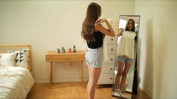 Chica alta tratando de usar un vestido
