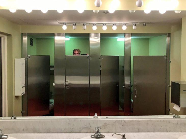 Chica alta asomándose por un baño público