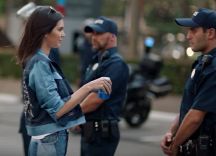 mujer con pepsi y hombre policia