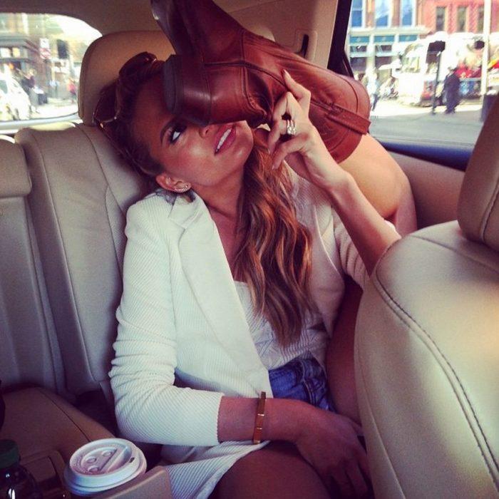 mujer sentada en coche levantando botas