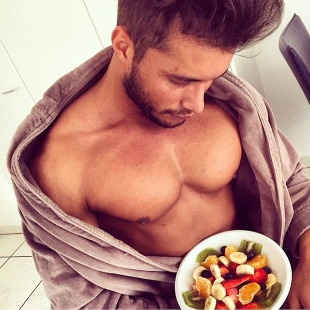 hombre sin playera comiendo fruta