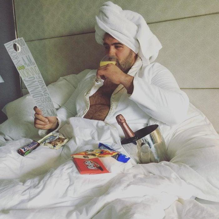hombre con bata de baño y toalla acostado en la cama