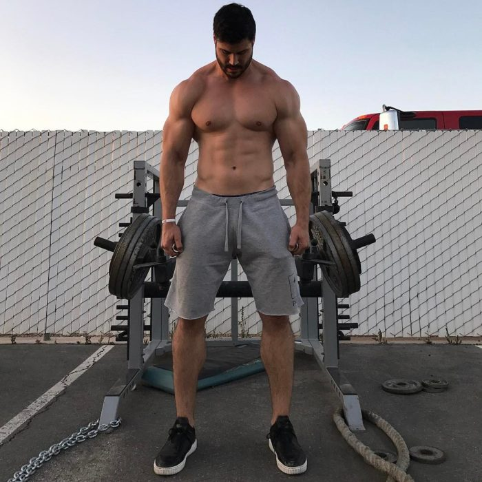 hombre sin playera y aparatos de gimnasio