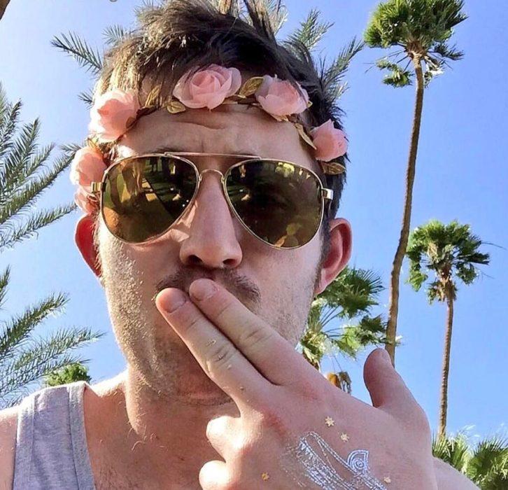 hombre con lentes y corona de flores