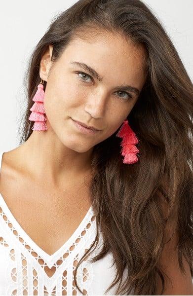 Chica usando unos aretes color rosa