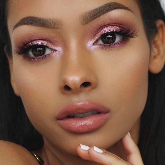 Chica usando un labial en tono rosa