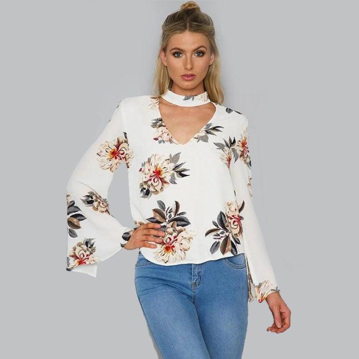 mujer rubia con blusa blanca de flores