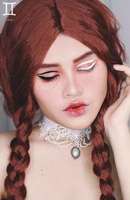 mujer con cabello rojo y maquillaje