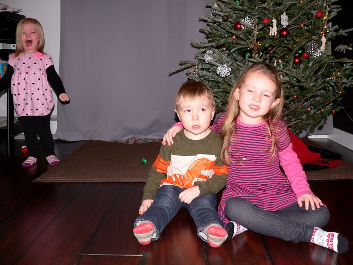 niños sentados junto al árbol